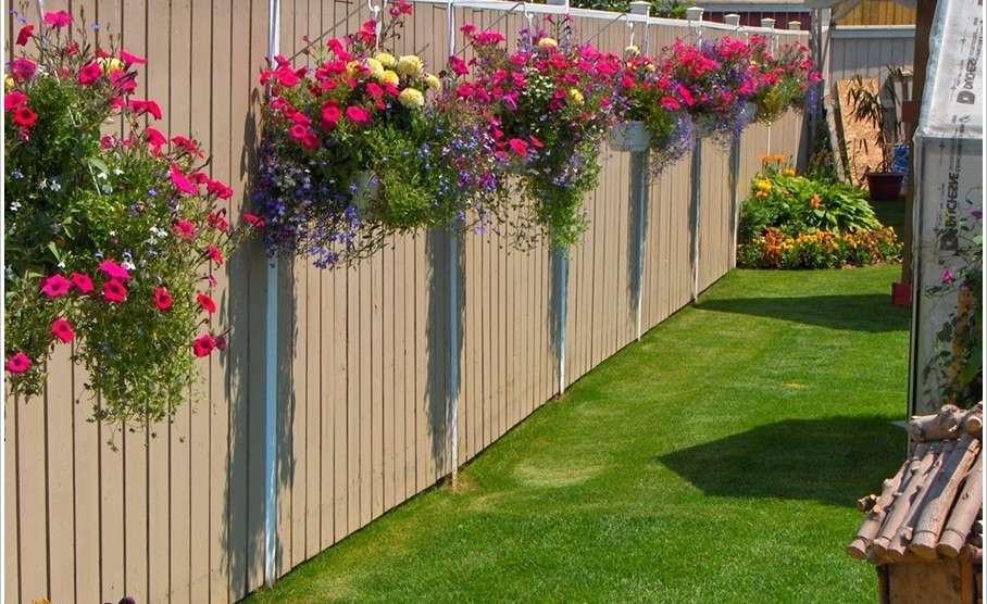 Интересно оформить сад, дачу или огород вы можете путем декорирования забора. Отличный вариант — подвесное кашпо с цветами.