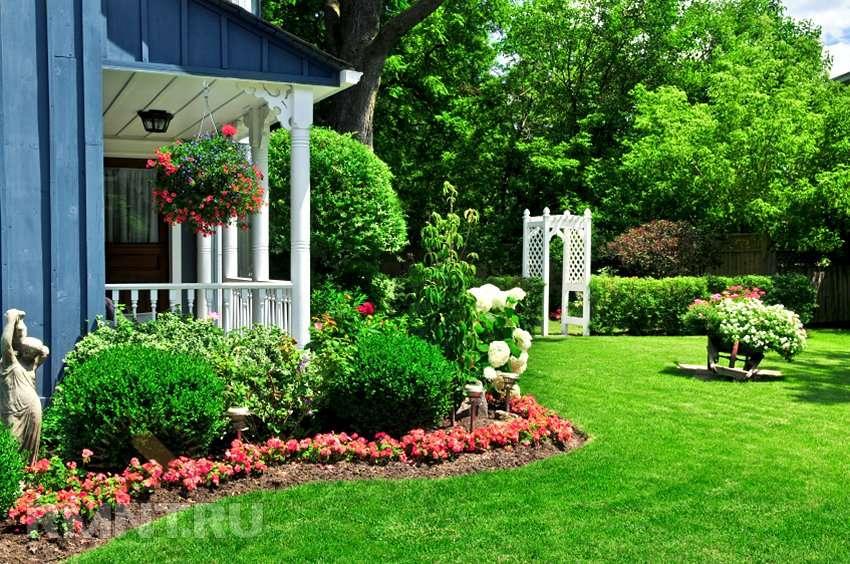 Дом находится в глубине дачного участка в окружении цветов.