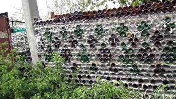 Укладывайте бутылки поперек стены забора горлышками во двор и соединяйте раствором