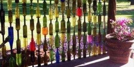 Путем нанизывания стеклянных бутылок на металлический прут можно получить высокодекоративное ограждение для дачи.